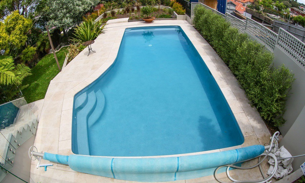 Big backyard swimming pool, Mid blue pool water beadcrete santorini, travertine pool coping and tiling, glass pool fence and gardens surrounding.