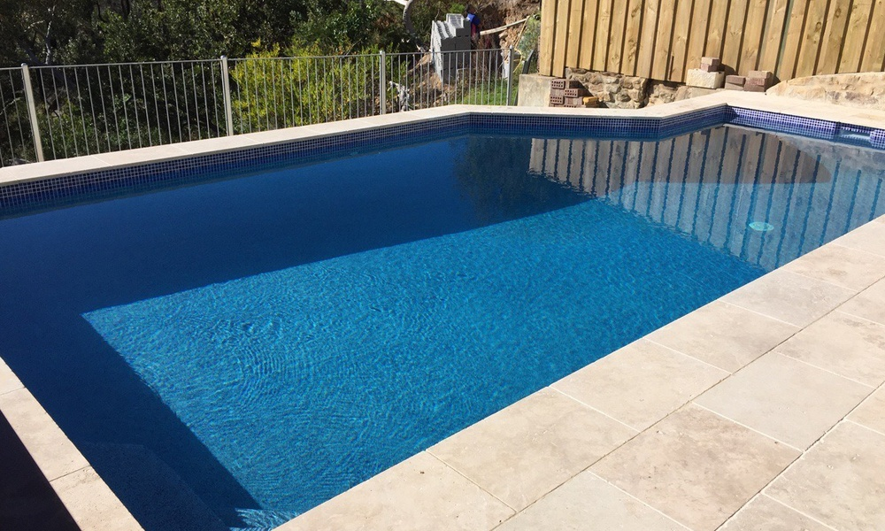 Beautiful dark blue backyard swimming pool, new pool finished with capri beadcrete interior, dark blue mosaic waterline tiles, travertine coping surrounds