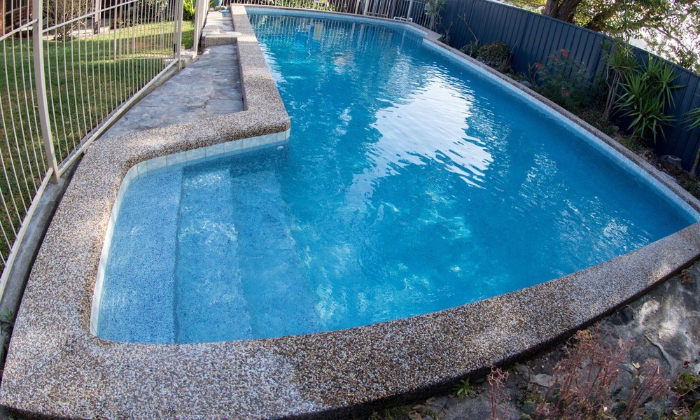 Big backyard pool, new dark blue pool interior, Beadcrete Capri, old pebblecrete pool coping and a old aluminium pool fence.
