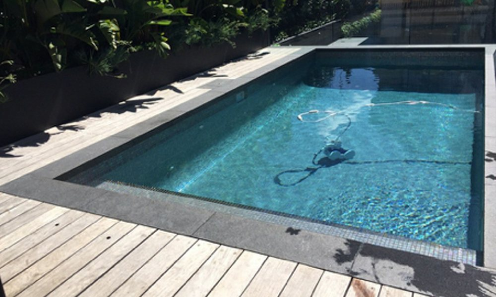 Dark blue pool water, Bluestone pool coping with timber deck. Backyard pool.
