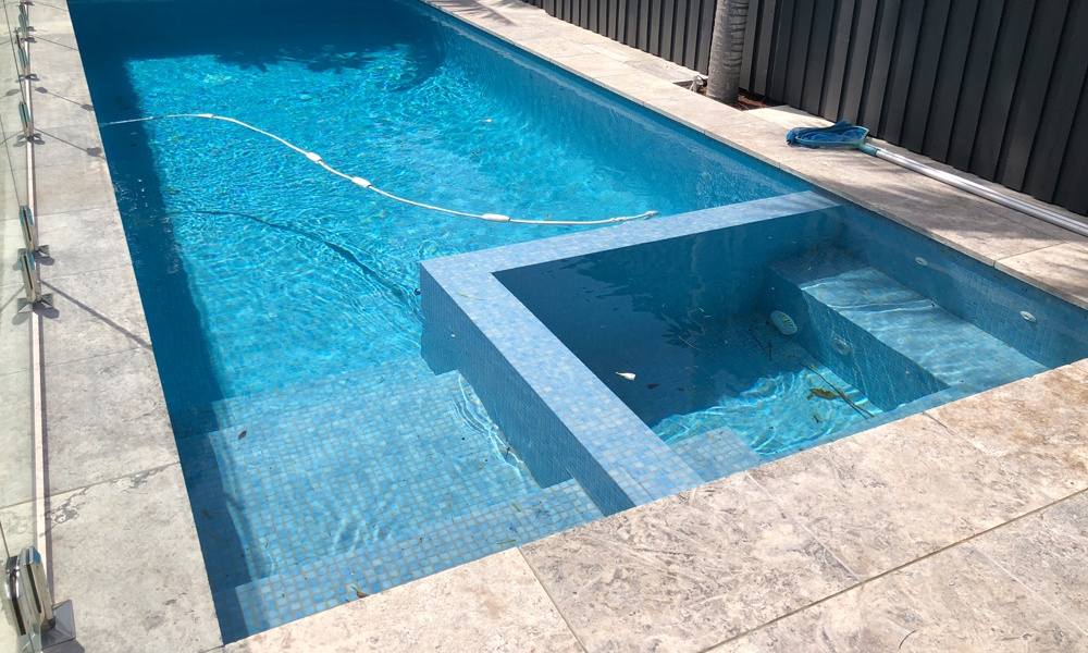 Fully tiled swimming pool and spa. Travertine pool coping.