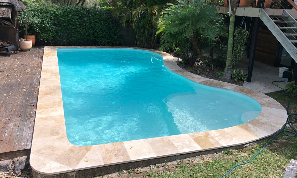 Kidney shaped old swimming pool, renovated to a modern travertine coping, white ezarri waterline tiles and white pebblecrete interior. Deck to one sideband garden bushes surrounding.