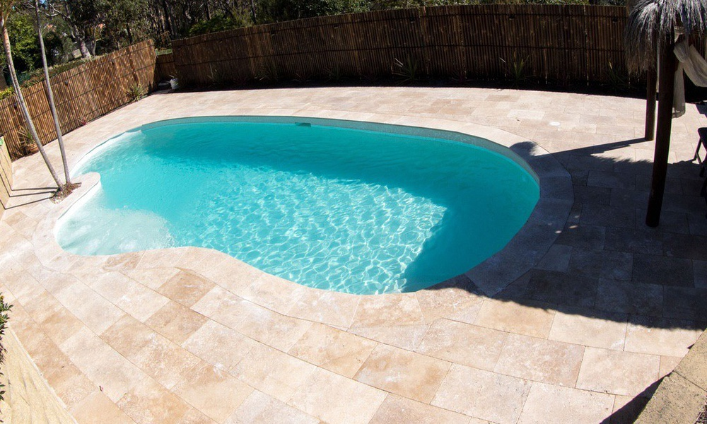Tropical backyard pool, palm trees with light blue pool interior, beadcrete sedona, Travertine coping and paving.