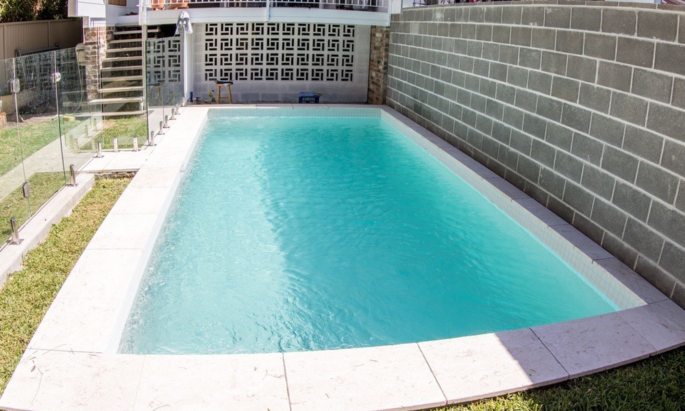 Duplex swimming pool, modern pool, white travertine coping with white pebblecrete glass interior, glass pool fence.