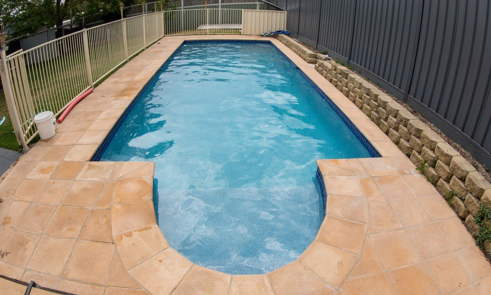 Rectangle swimming pool with a semi circle seat at the end, mid blue pool water, glass pool interior Beadcrete, sandstone pavers with retaining wall.