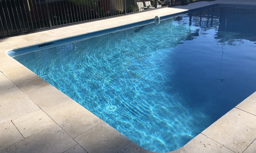 Blue pool water, return line pushing pool water to skimmer box, glass pool interior, beadcrete hayman, custom travertine coping tiles.