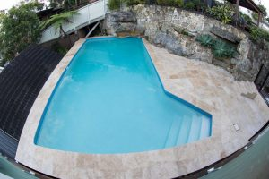 Travertine pool coping and tiled surroundings, blue pool, backyard pool renovation