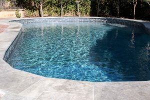 Dark blue pool water, Beadcrete interior with black waterline tiles, Limestone pool coping