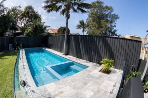 Tropical backyard swimming pool, Fully tiled pool with travertine tiles surrounding, glass pool fence.