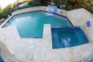 Travertine coping tiles with Beadcrete spa interior amongst existing pebblecrete pool.