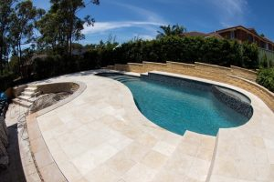 Limestone pool coping and surrounding tiling with a Beadcrete Venizia interior. Backyard pool renovation