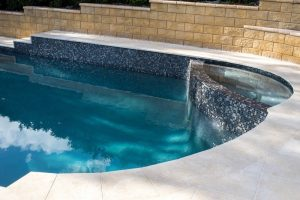 Ezarri tiled waterline tiles and wet edge spa, dark blue pool water, limestone pool surrounds.