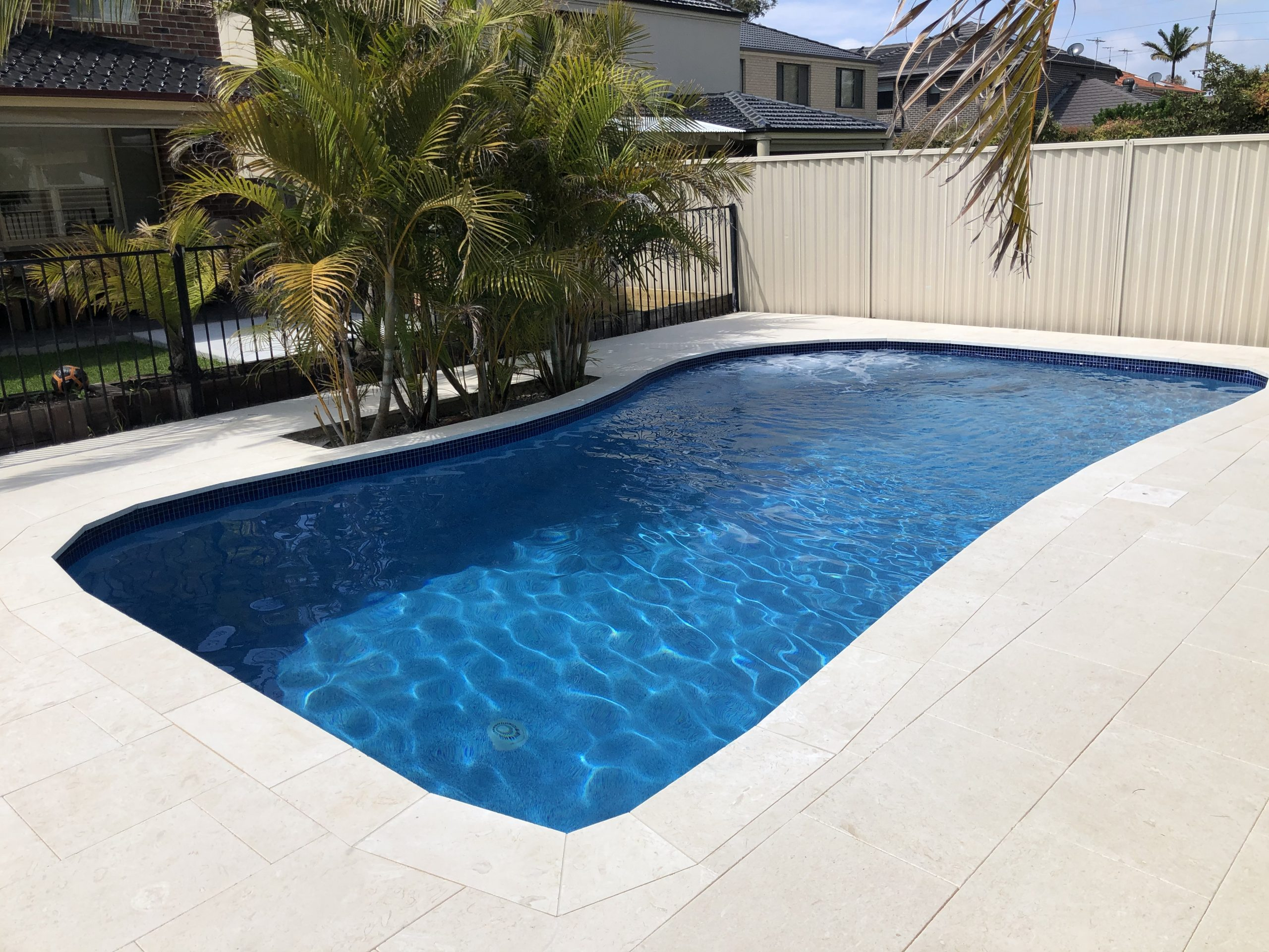 Palm tree pool renovation with new tiles and dark blue beadcrete water.